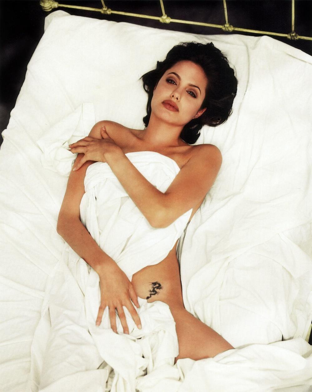 Анджелина Джоли горячие с томным взглядом голая лежит в белой постели немного прикрывшись простыней
