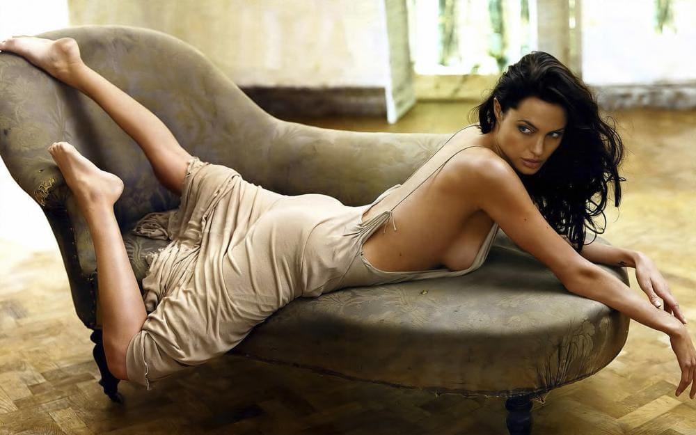 Анджелина Джоли фото лежит на животе на мини диване, светлый сарафан на лямках, оголенная спина, плечи, ноги ступни