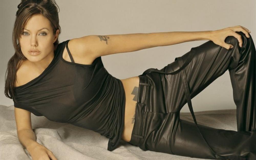 Анджелина Джоли горячие лежит на боку в кожаных черных штанах от бедра и черной майке