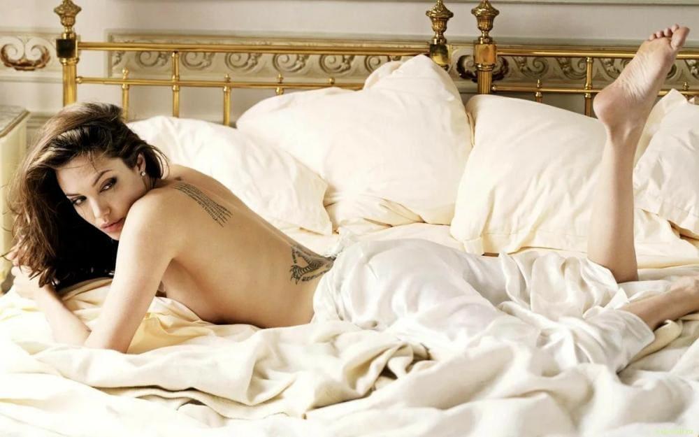 Голая Анджелина Джоли лежит на животе в кровати, белая постель, слегка прикрыта покрывалом одна нога согнута в колене, ступня
