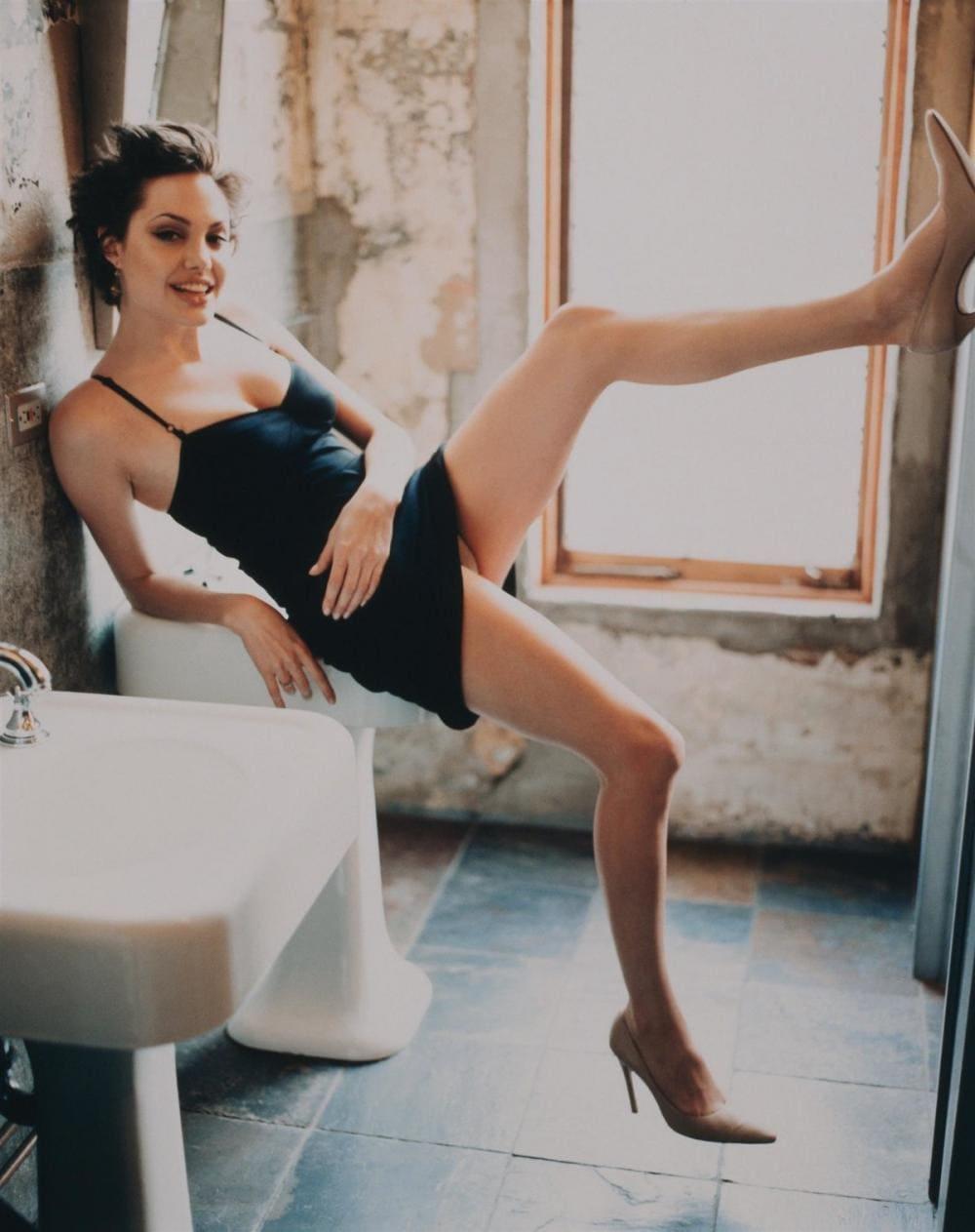 Анджелина Джоли фото фото бурной молодости на унитаз облокотилась в коротком черном пеньюаре, одна нога задрана на стену, ножки оголены,каблук