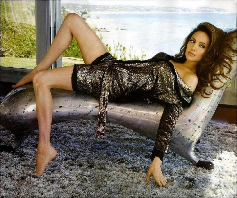 Анджелина Джоли горячие лежит на софе в платье под змеинную кожу, плечо оголено, юбка задрана, ножки оголены, носочки вытянуты