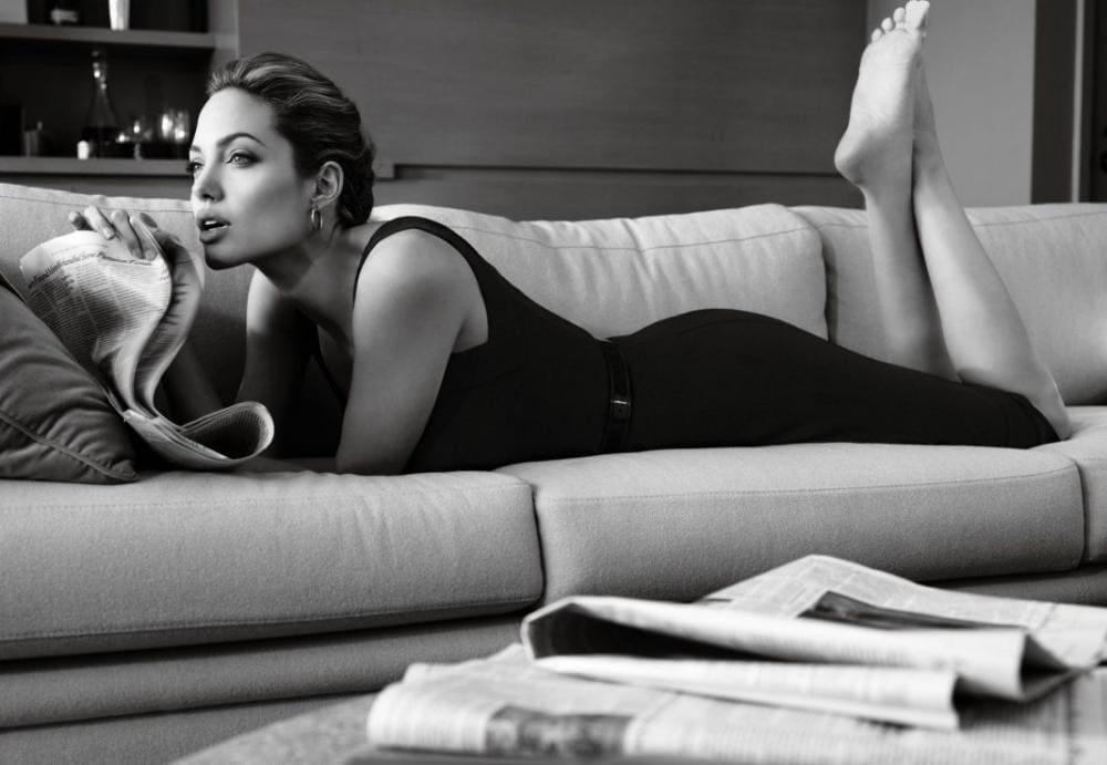 Анджелина Джоли горячие черно-белон фото на животе лежит на диване,в черном платье, ноги согнуты, ступни