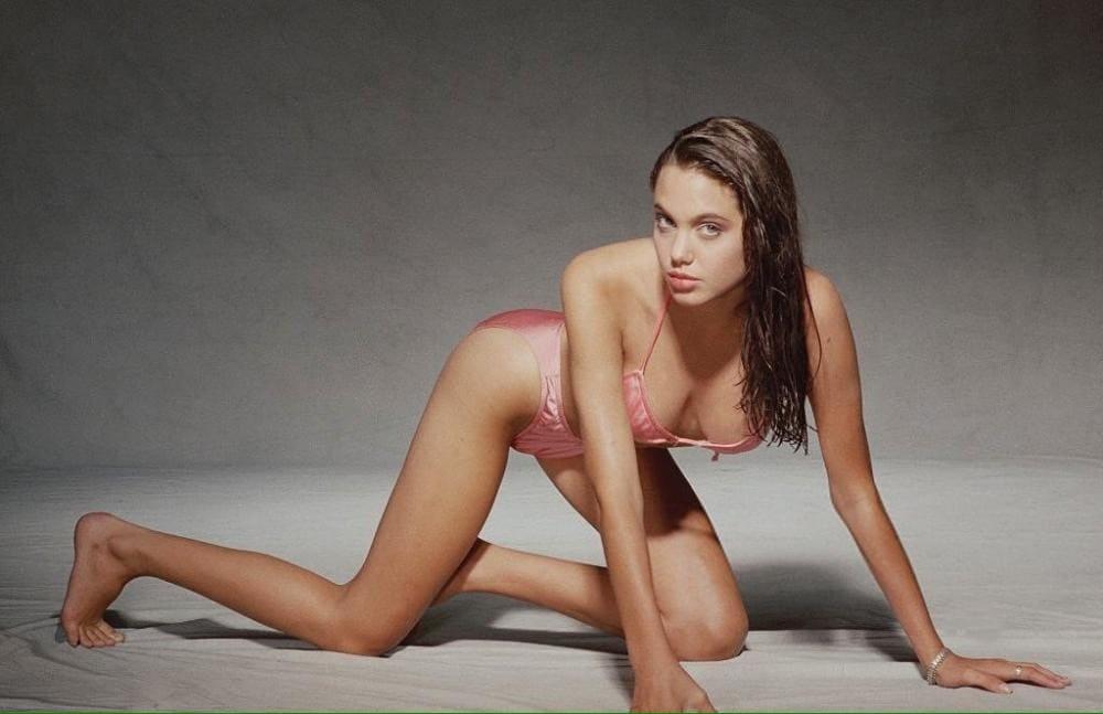 Анджелина Джоли в купальник розового цвета, стоит в позе собаки