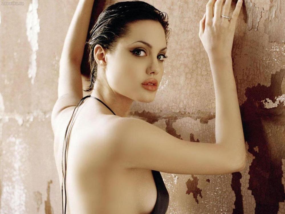 Анджелина Джоли горячие стоит возле стены подняв руки на стену, обнаженная спина