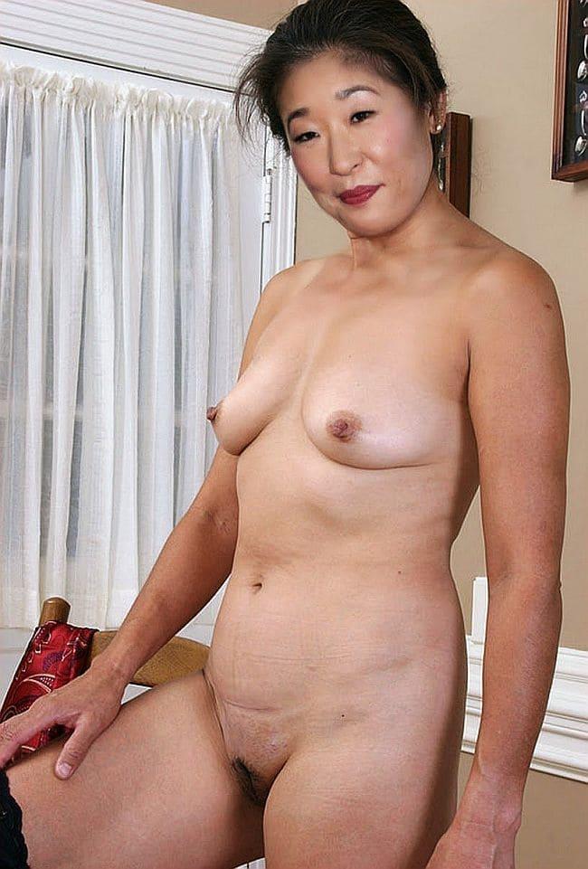 Фото зрелой азиатки с маленькими стоящими сиськами пизда имеет интимную стрижку, стоит в комнате, за позади кровать, окно закрыто белыми шторами, волосы прибраны, похотливо и призывно смотрит слегка улыбаясь