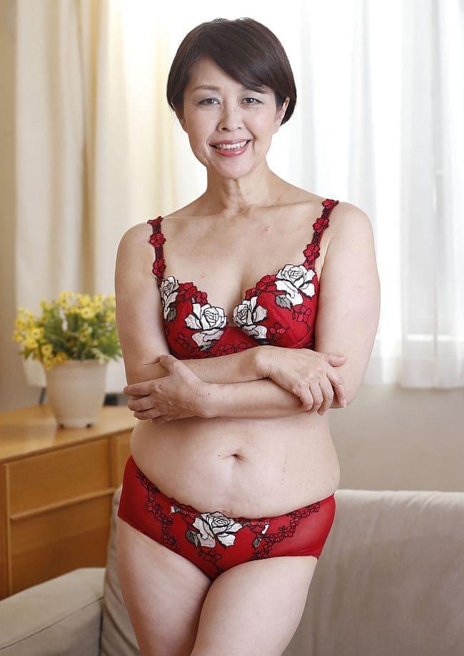Красивая зрелая азиатка фото в нижнем белье стоит сложив руки на животе в комнате с цветком на тумбочке и занавешенном белой легкой занавеской шторой