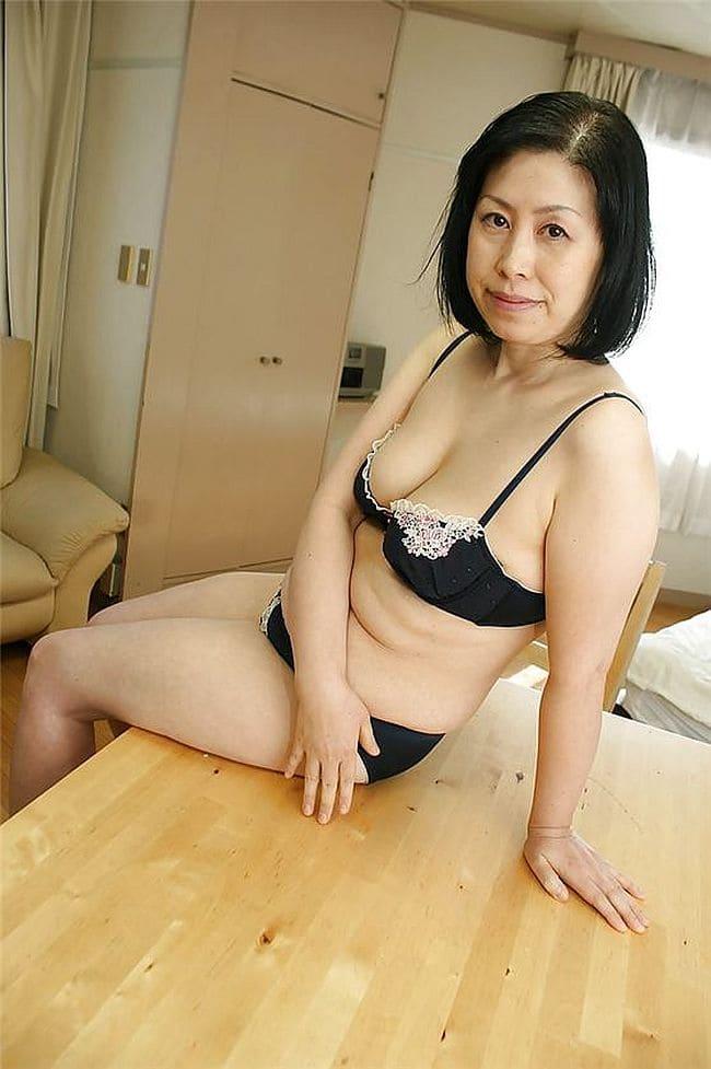 Зрелые женщины азиатки фото сидит на столе в нижнем белье черного цвета.