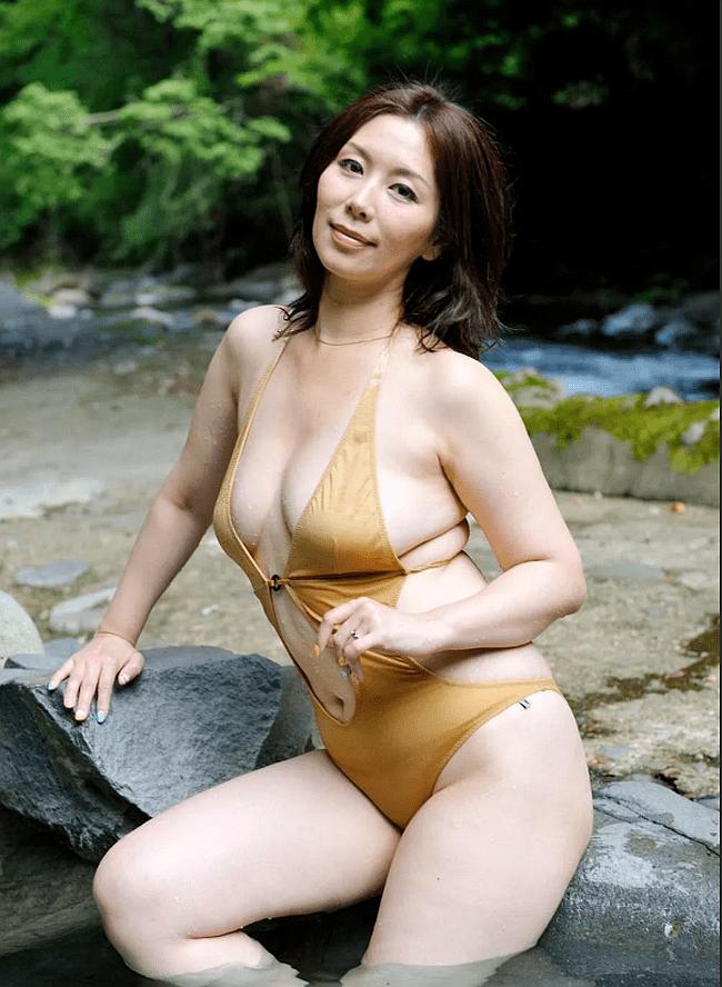 Зрелые азиатки фото женщины в светло-коричневом купальнике сидит на бортике в прудике обнесенном каменными берегами