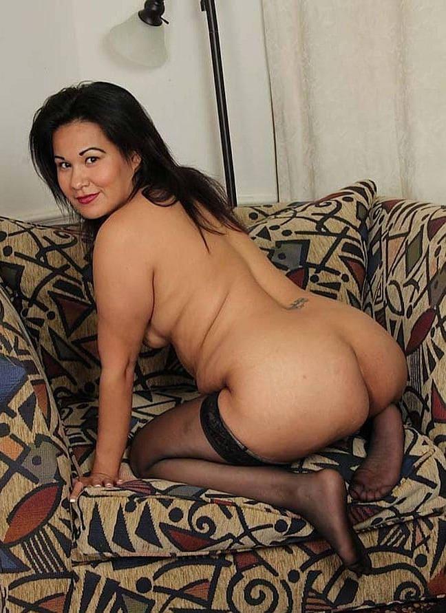 Зрелая азиатка в чулках стоит раком в широком кресле, миловидное лицо, приятная улыбка и похотливый призывный взгляд