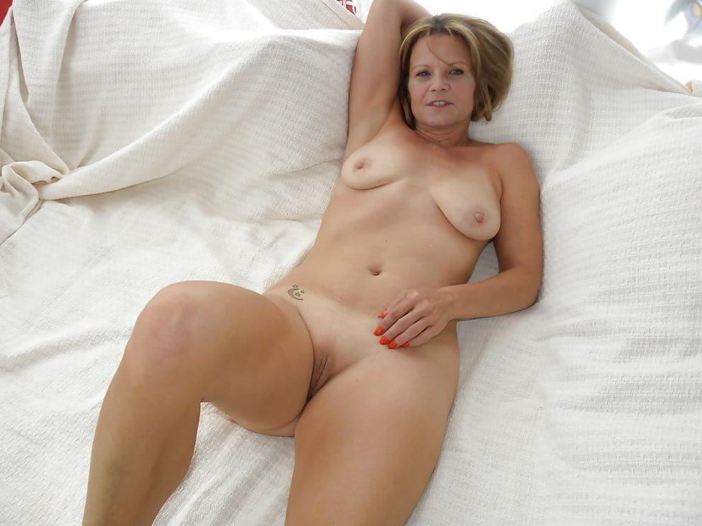 Голые зрелые тетки лежит на кровати, правая рука закинута за голову, одна нога согнута в колене, тату на правом боку