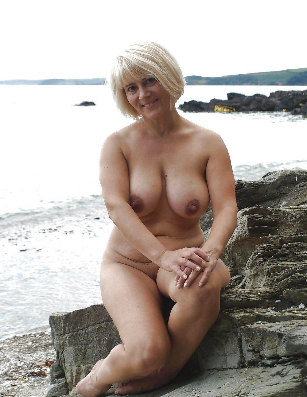 Красивые голые тетки блондинка с короткой стрижкой сидит на камнях возле кромки воды у моря.
