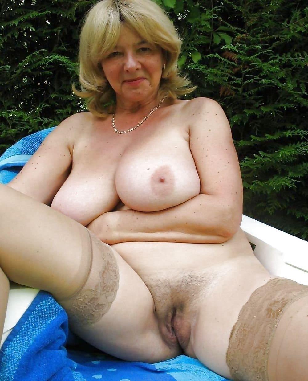 Голые тетки порно блондинка с большими сиськами в светлых чулках сидит раздвинув ноги, показывает небритую пизду