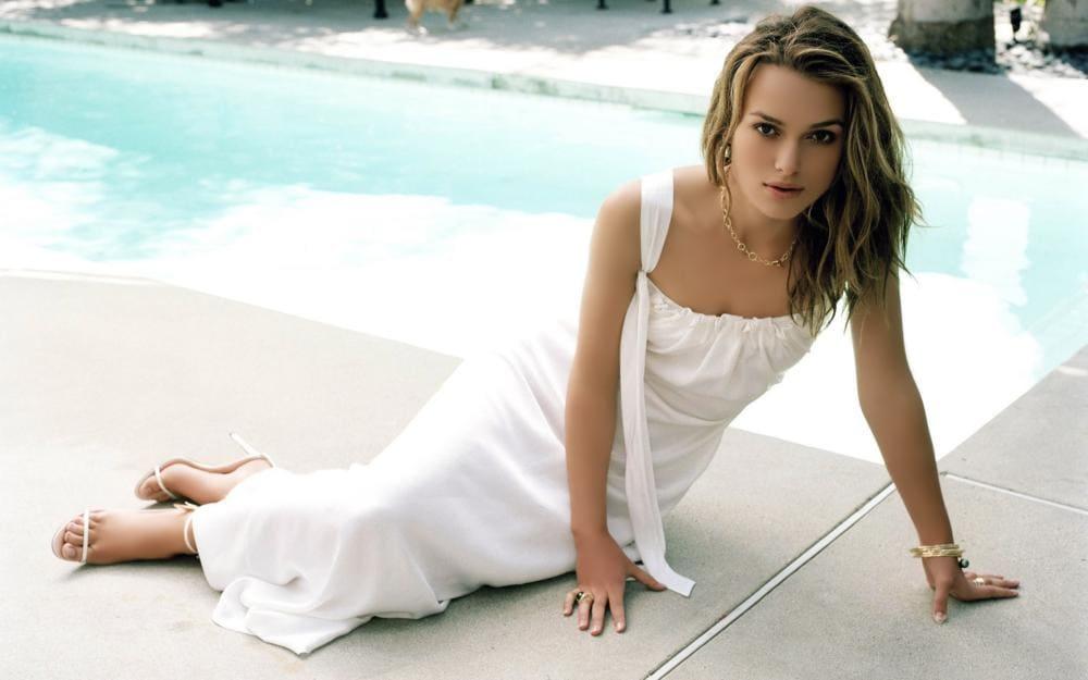 Фото Кира Найтли в белом платье и босоножках сидит возле кромки бассейна упираясь на руки