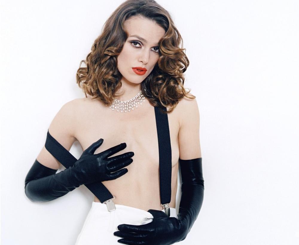 Фото Кира Найтли стоит в черных длинных перчатках, широкие подтяжки одну грудь прикрыла рукой, яркий макияж