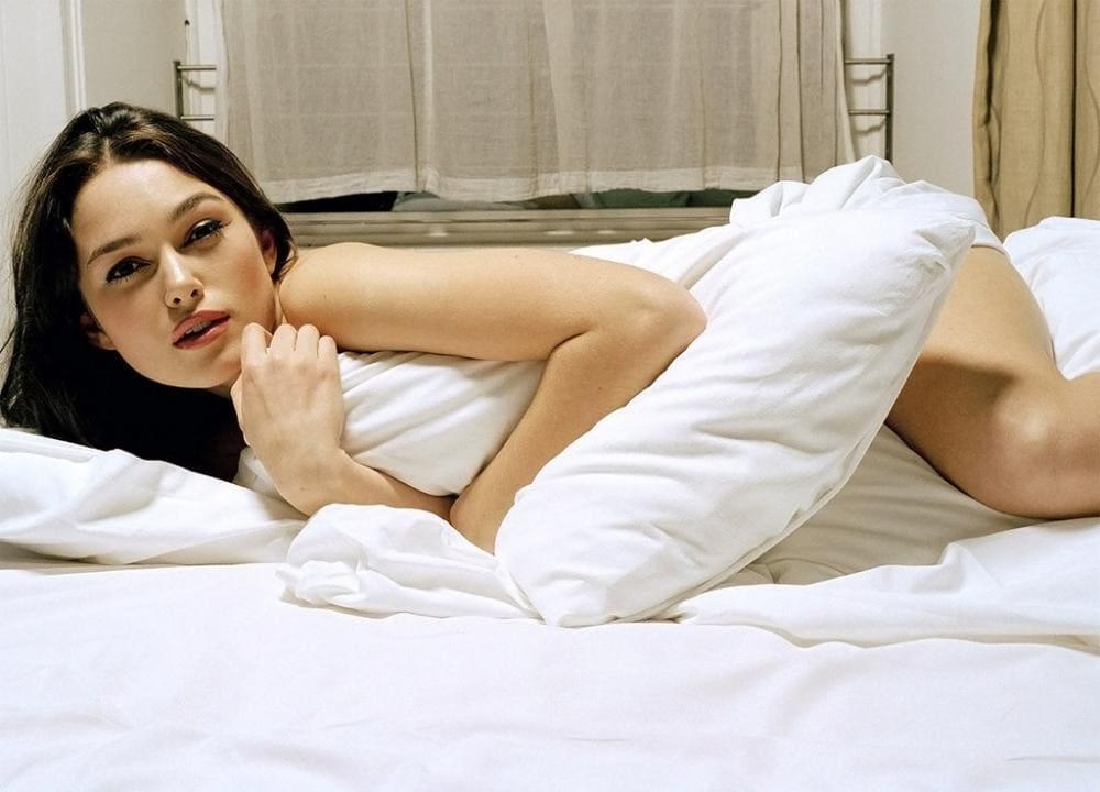 Кира Найтли обнаженная лежит на кровати прикрываясь подушкой