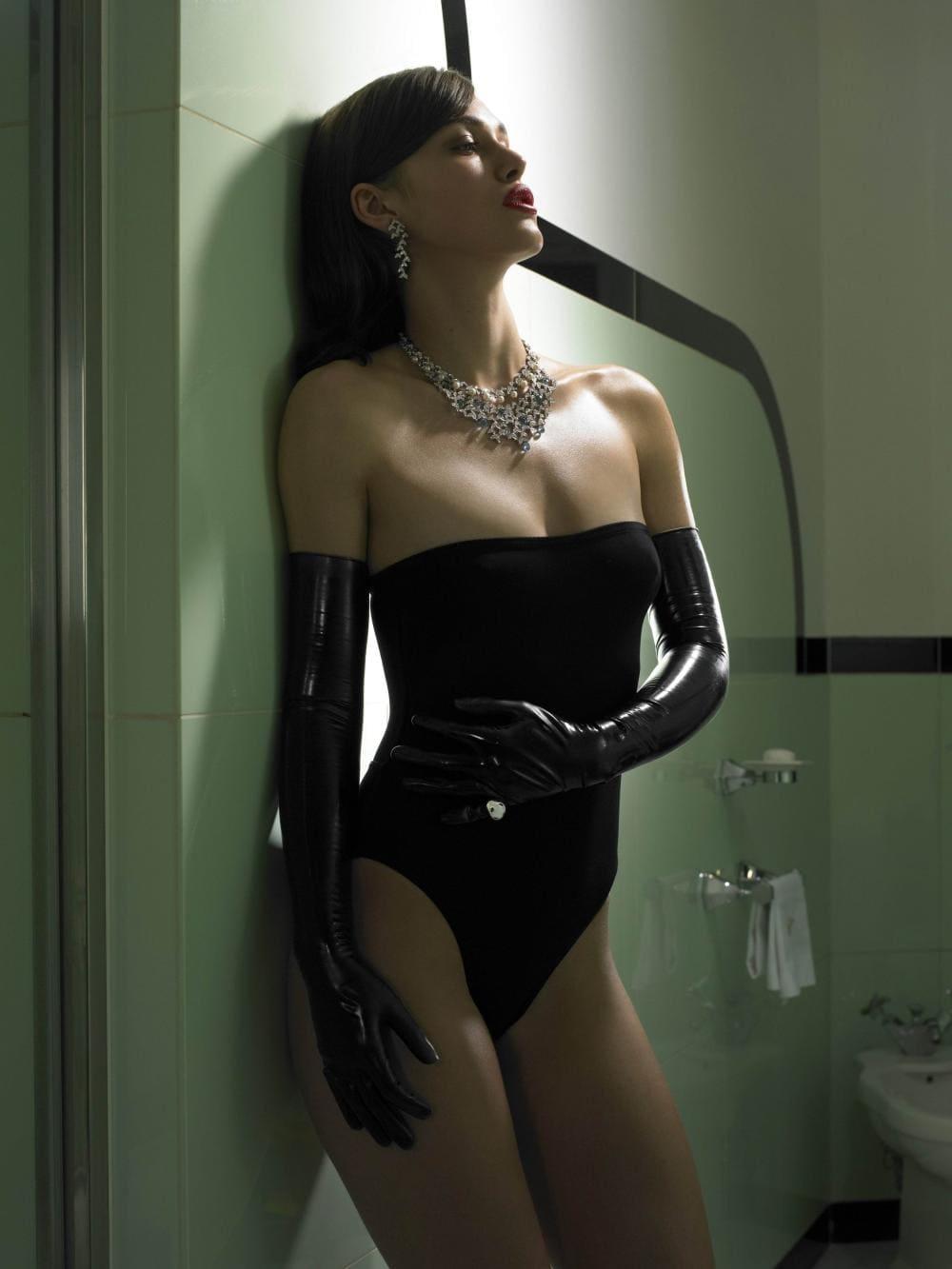 Кира Найтли лучшие стоит прислонившись к стиене в черном сплошном купальнике из латекса и длинных перчаток, на шее ожерелье