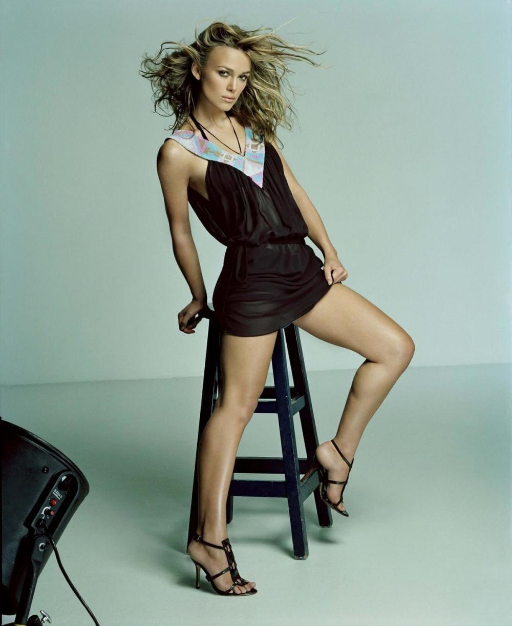 Фото Кира Найтли стоит слегка оперлась на высокий табурет в черном очень коротком платье, босоножки на высоком каблуке