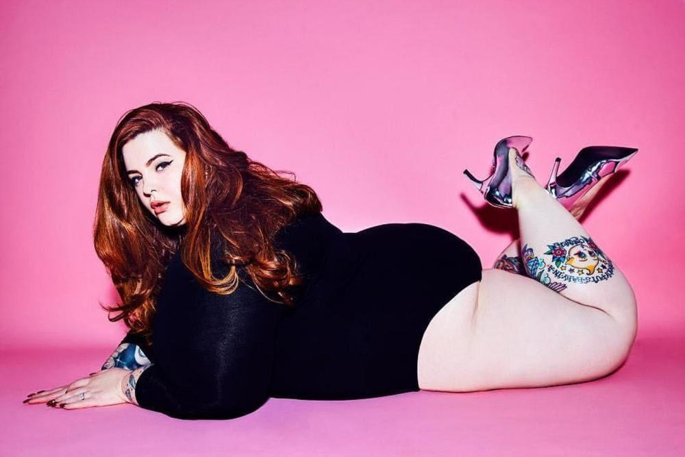 Самая толстая модель Тесс Холидей лежит на животе на полу в черном комбидрессе, ножки сексуально согнула в коленях, туфли на шпильке