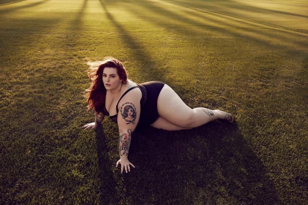 Тесс Холидей в купальнике лежит упершись на руки в поле