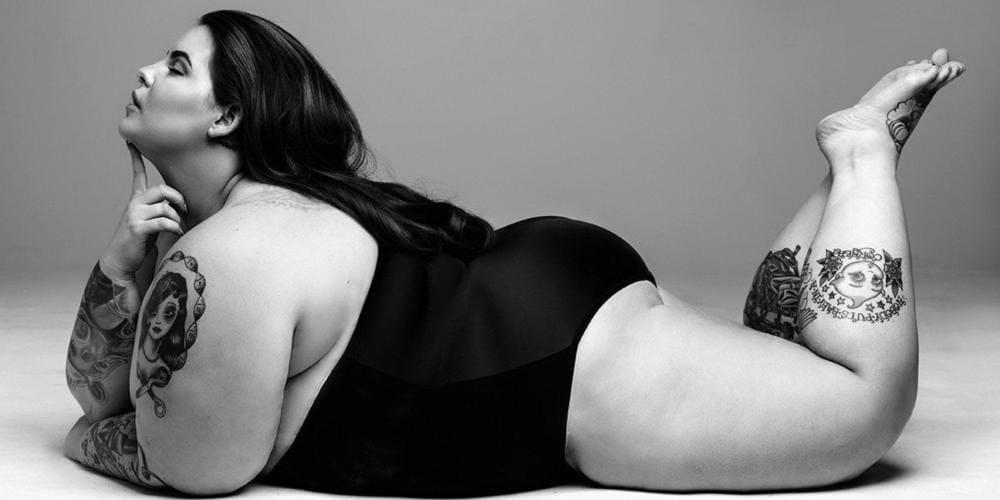 Тесс Холидей в купальнике лежит на животе ноги согнуты в коленях подняты, пальцем упирается в подбородок, фото черно-белое