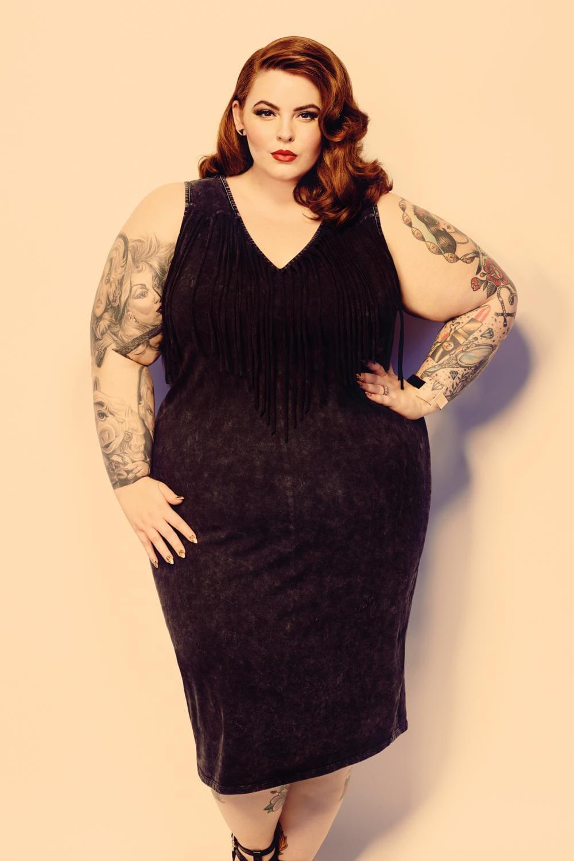 Самая толстая модель Тесс Холидей в черном платье стоит, левая рука на талии, макияж