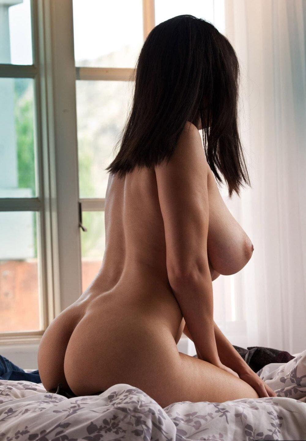 Фото голых брюнеток сидит на кровати на коленях вполоборота, лица не видно, вид сбоку