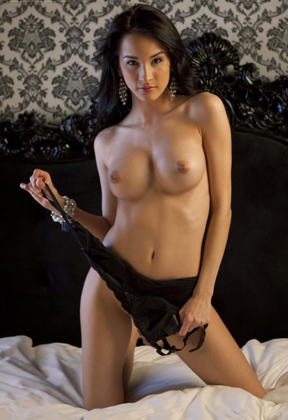 Голые груди брюнеток стоит на кровати на коленях молодая девушка в руках растягивает бюстик