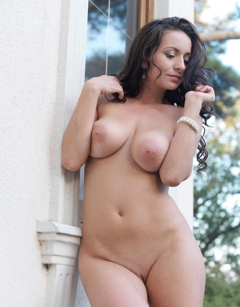 Голые груди брюнеток стоит возле окна на улице на руке браслет