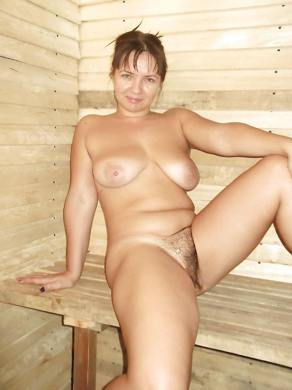голые бабы в бане сидит на деревянной скамейке подняв левую ногу и раздвинув, показывает свою мохнатую пизду