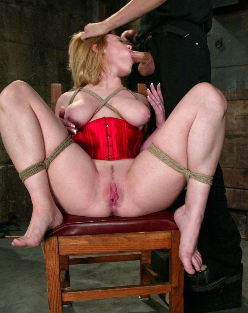 порно зрелые бдсм блондинка в красном корсете сидит на стуле , бондаж, ноги раздвинуты, птзда раскрыта, сосет член