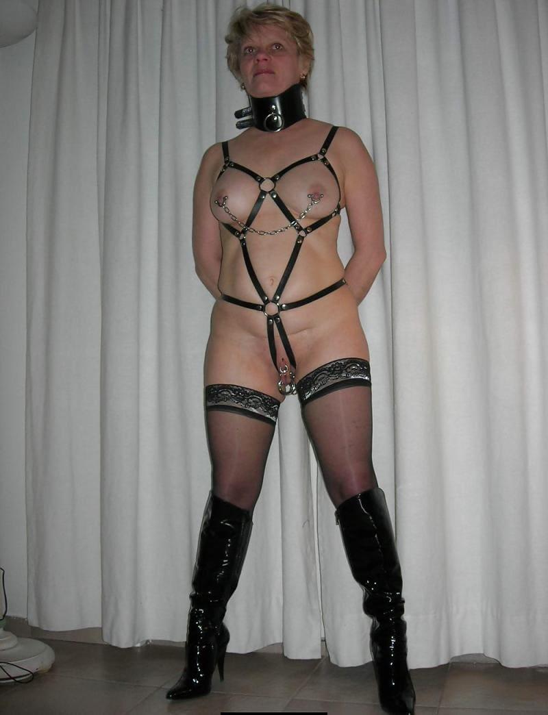 бдсм зрелые рабыни блондинка с короткой стрижкой стоит голая, кожаный бандаж, широкий ошейник на шее, чулки высокие сапожки
