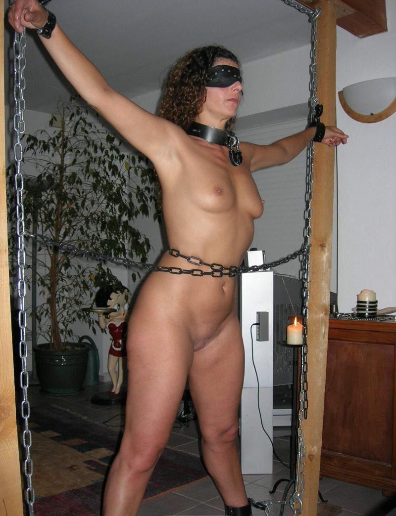 бдсм зрелые голая черная маска на глазах, на шее ошейник с замком, обмотана цепями и прикована за руки и ноги