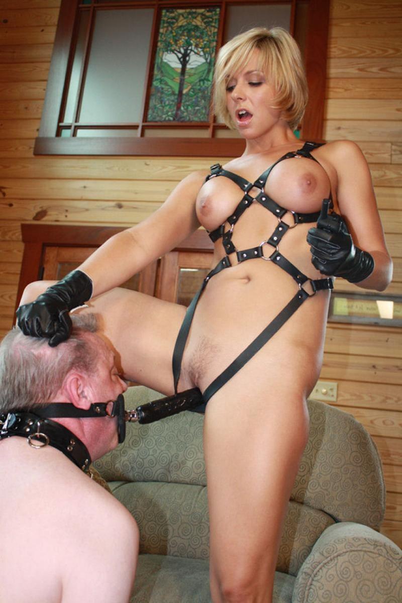 зрелая госпожа бдсм голая в бандаже, в черных кожаных перчатках держит за волосы пожилого раба на нем ошейник, кляп на сбруе с фаллосом заставляет ебать себя в пизду