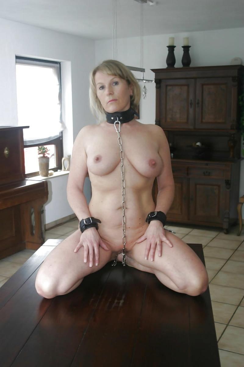 бдсм зрелые рабыни голая блондинка кожаный ошейник на цепи на руках кожаные наручники, сидит на коленях на столе