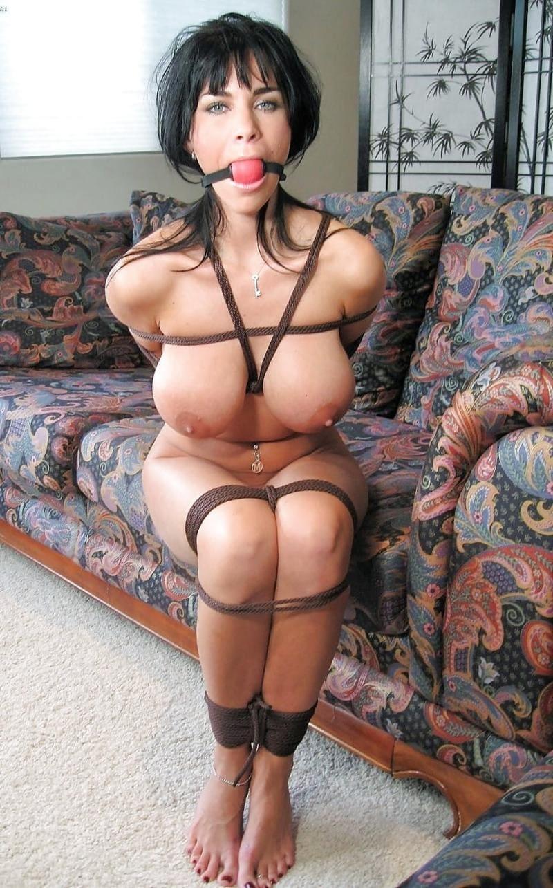 бдсм зрелые брюнетка голая с кляпом во рту голая сидит на диване связанная, большие сиськи