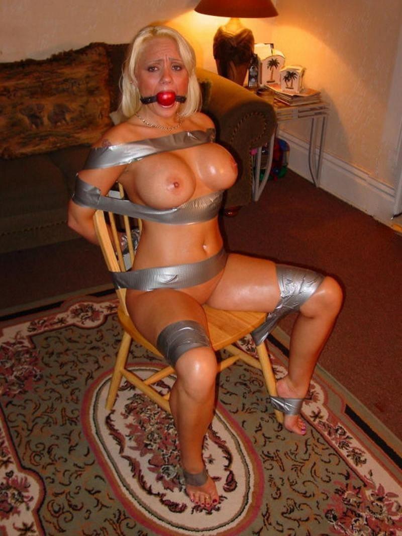 бдсм зрелые фото блондинка с кляпом во рту связана серебристой виниловой лентой, голая сидит на стуле привязана к нему голая, большие сиськи