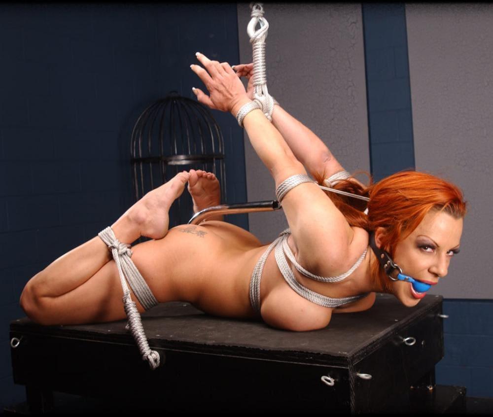 бдсм зрелые рыжая голая с кляпом во рту, лежит на пыточном столе, бондаж, руки заведены за спину и привязаны кверху