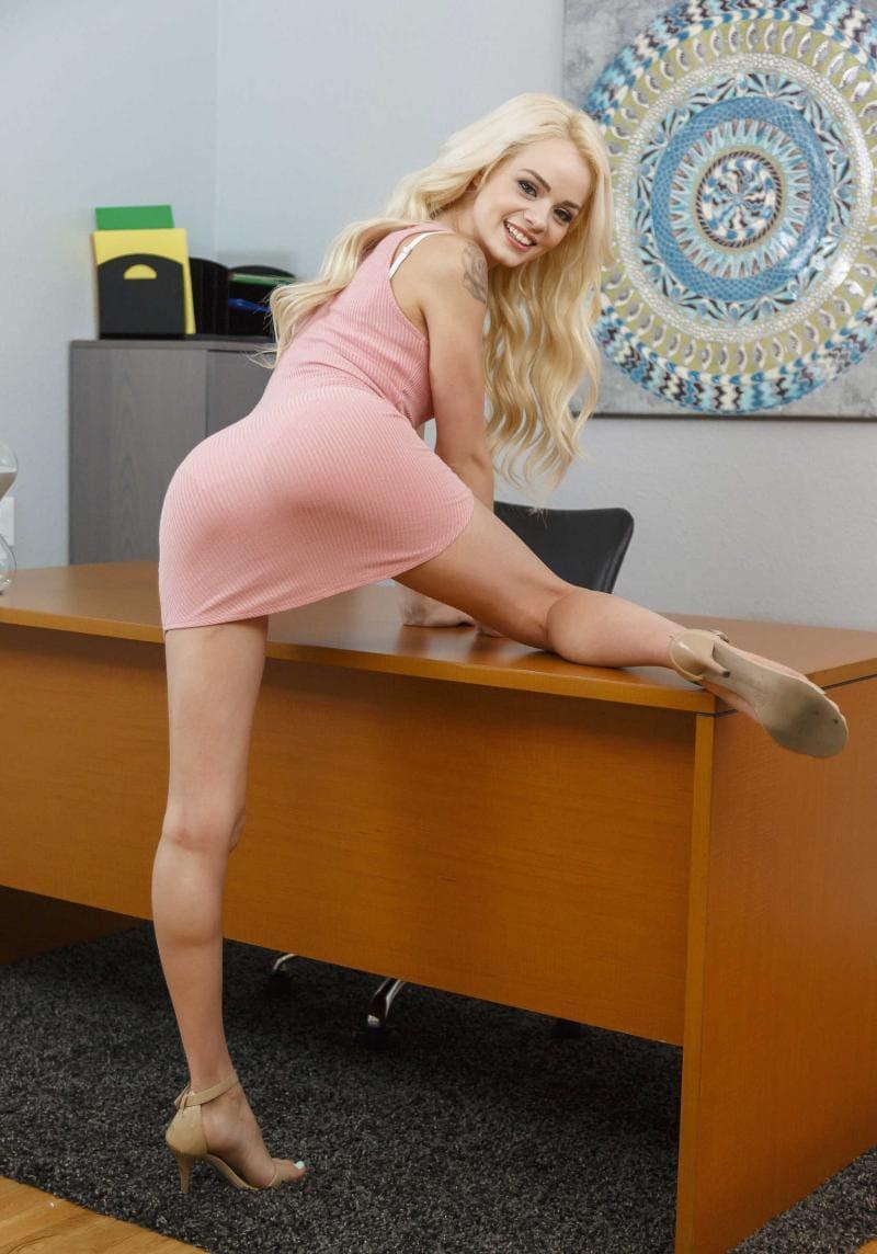 Эльза Джин фото в розовом обтягивающем платье стоит у стола развернувшись задом закинув ногу на стол