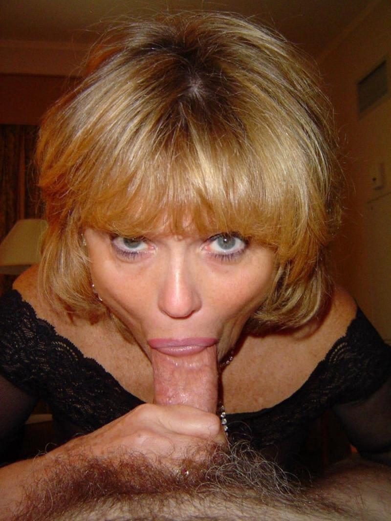 зрелая делает минет блондинка держит в руках хуй и сосет, губы плотно обжимают половой орган мужчины, взгляд прямо в камеру, галаза серого цвета, стрижка короткая.