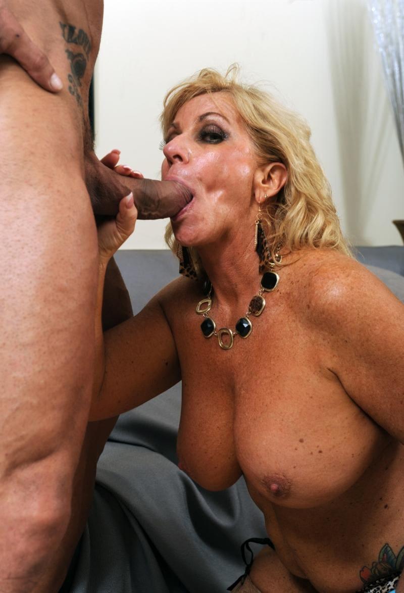 порно минет зрелых женщин блондинка голая стоит на коленях с большими сиськами с ожерельем на шее и сосет толстый большой хуй