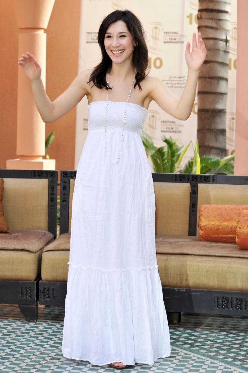 Сибель Кекилли фото в белом длинном платье стоит, глубокое декольте руки подняла вверх улыбается
