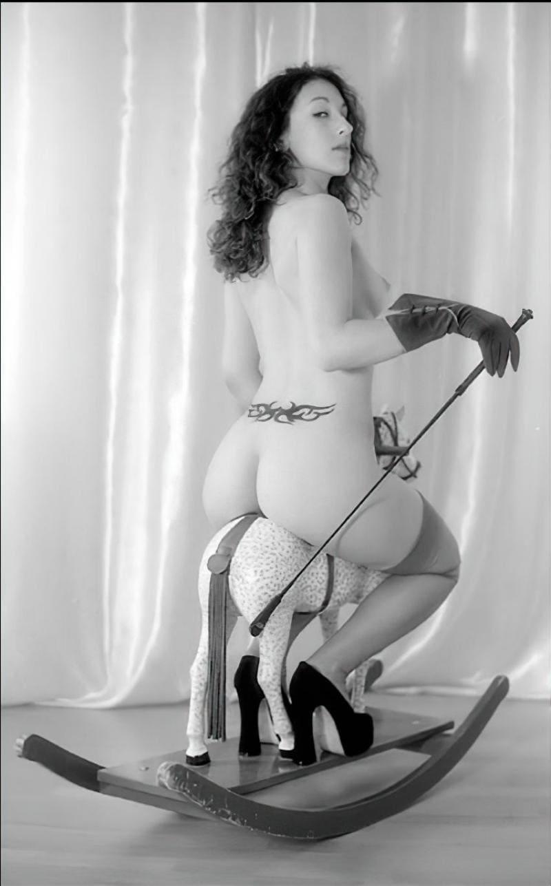 Сибель Кекилли БДСМ в роли госпожи сидит на качалке лошадке голая в длинных черных перчатках и туфлях на высоком каблуке с плеткой в руке