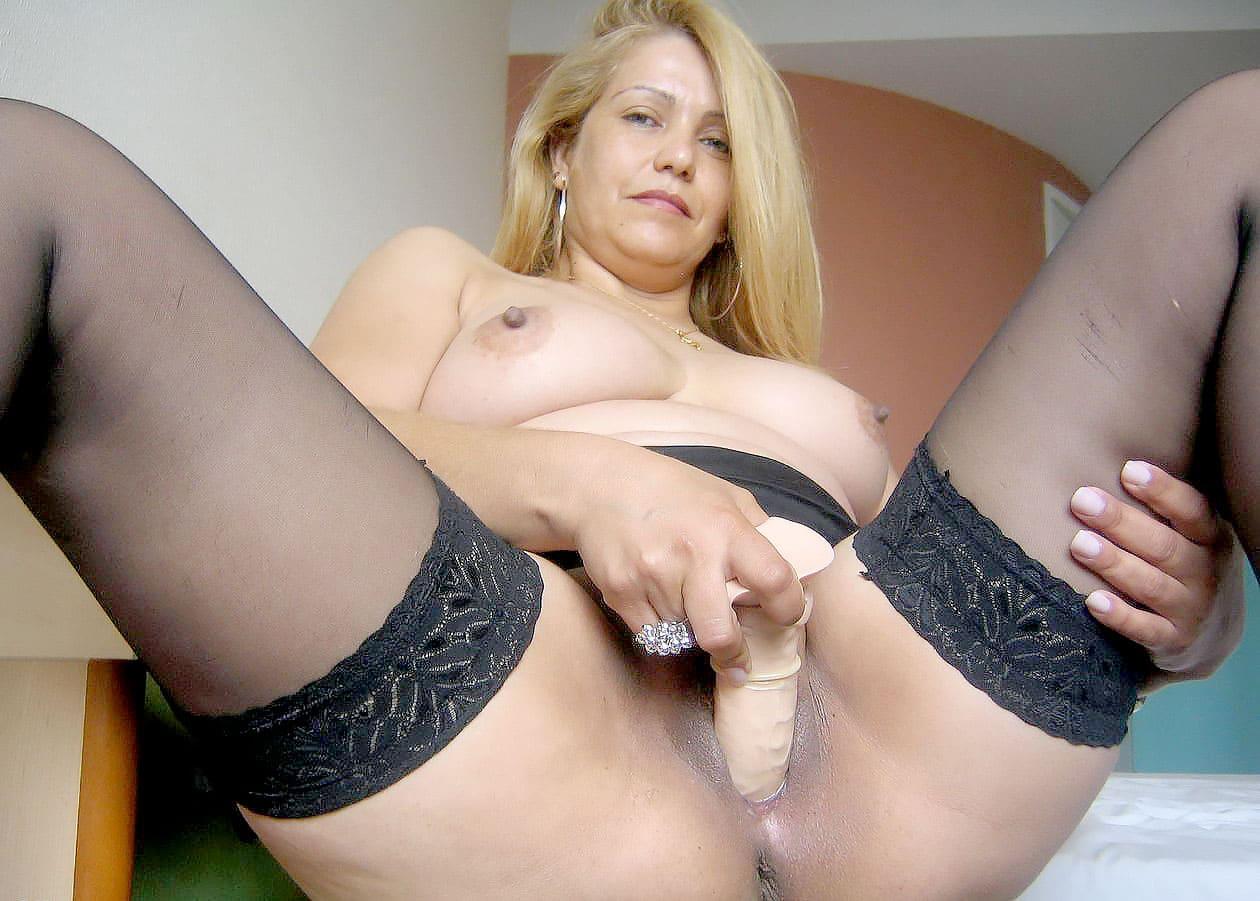Зрелые мастурбируют фото блондинки в черных чулках ебущей себя резиновым хуем сидя на краю кровати, красивая грудь с набухшими от возбуждения сосками торчит, волосы распущены, на безымянном пальце правой руки которой она орудует фаллоимитатором надет большой перстень, левой рукой придерживает ногу за ляжку, виден анус.