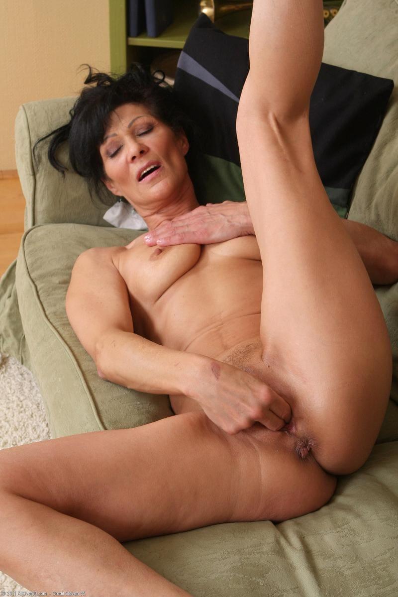 зрелые дамы мастурбируют голая брюнетка лежа на диване на спине левую ногу подняла вверх, правую отодвинула в сторону пальцами трахает пизду, рот открыт, на лице удовольствие, глаза прикрыты