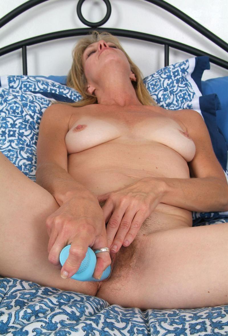 порно зрелые мастурбируют голая блондинка лежит на кровати на спине, раздвинула ноги, трахает себя вибратором и мастурбирует клитор