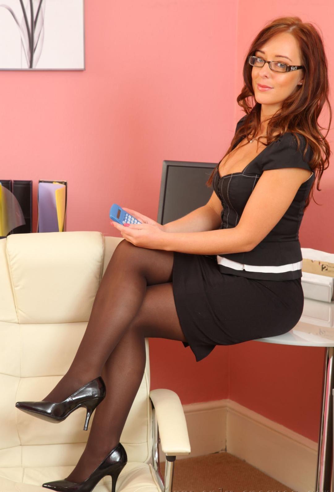 рыжая зрелая дама в очках в коротком черном платье сидит на столе ножки в колготках на каблуках поставила на кресло