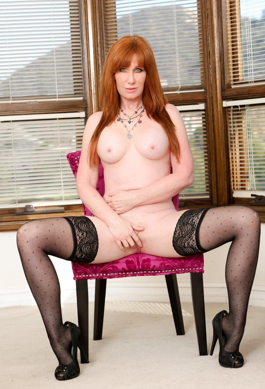 голая зрелая рыжая на стуле сидит раздвинула ноги в чулках на каблуке мастурбирует, на шее колье