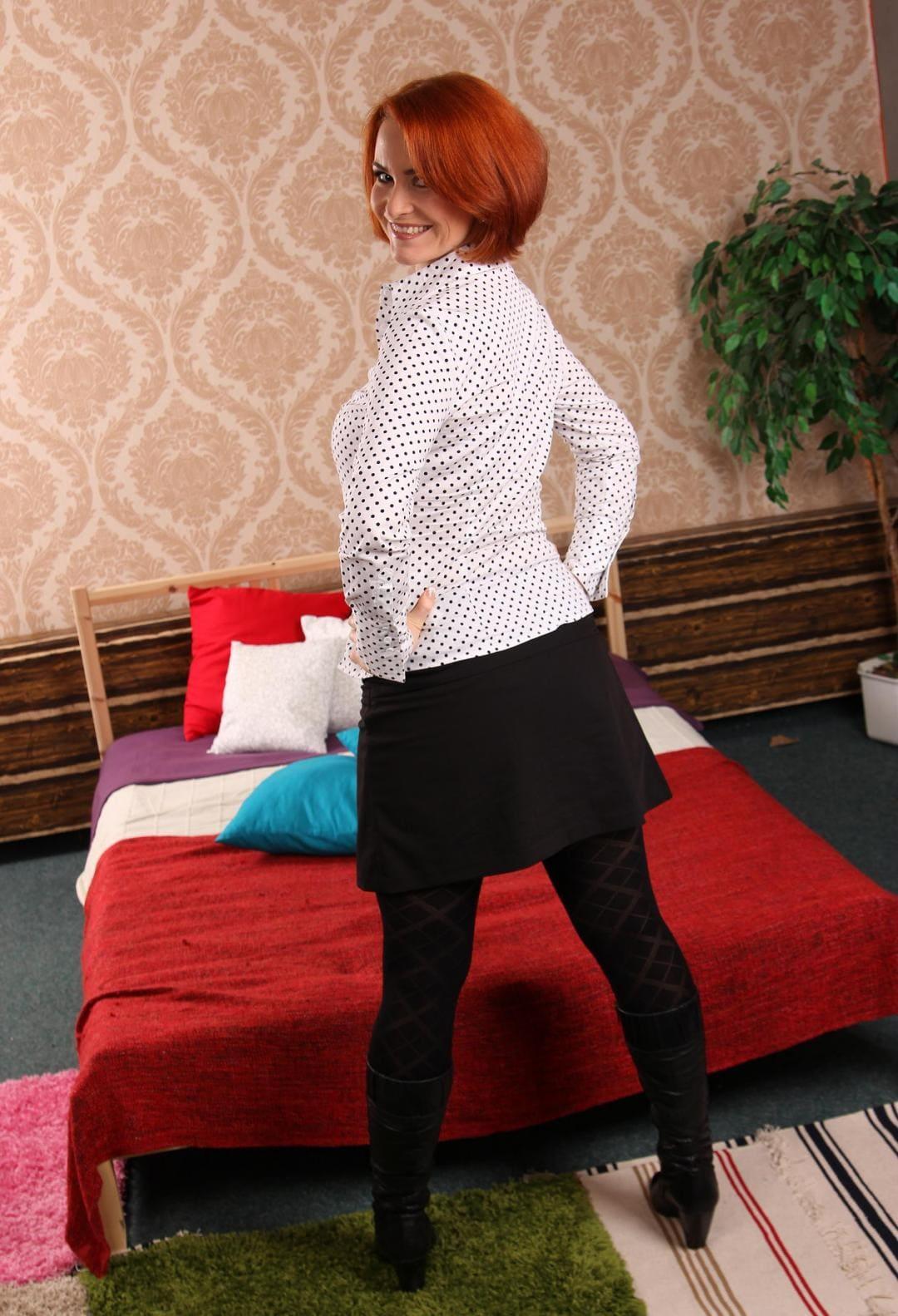 рыжая зрелая с короткой стрижкой стоит у кровати, в короткой черной юбке, плотных колготках, черных сапожках по колено ,немного повернулась, руки на талию положила улыбается