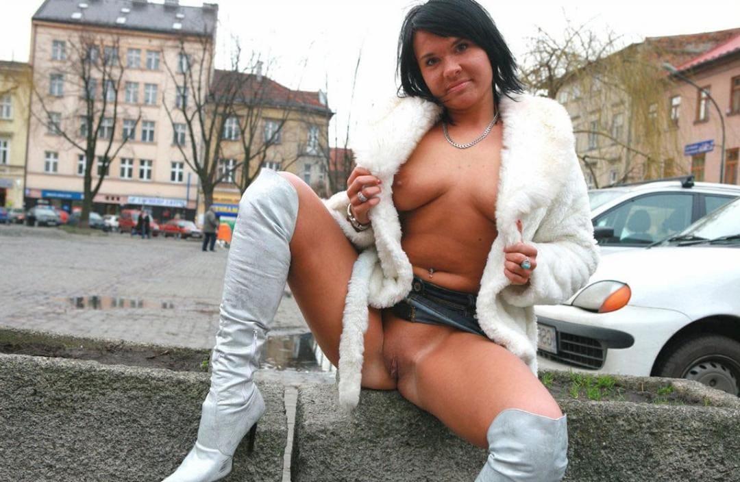 Зрелая дама брюнетка с короткой стрижкой в расстегнутом белом полушубке на голое тело сидит на парапете в высоких белых ботфортах, задрав правую ногу вверх